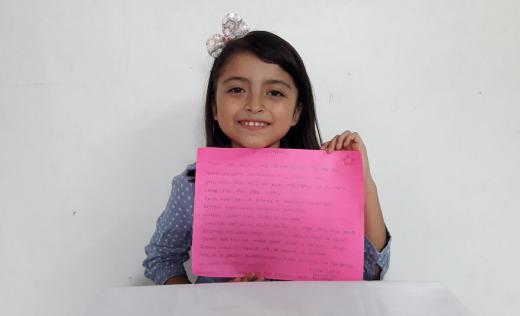 Vilma, 10, holds up her poem about coronavirus, Mexico