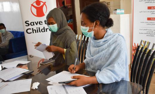 Two of Save the Children's volunteers are registering immigrants and refugees names for cash distribution.