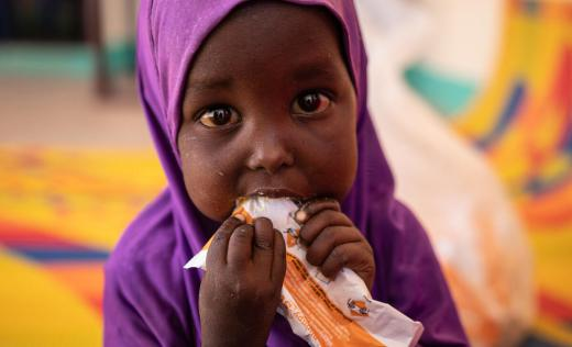 Salma (2) eats therapeutic food used to treat children with malnutrition at a Save the Children clinic in Somalia