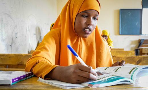 Farhiya, a 16 year old Somalian student wearing bright orange clothes, works at a schooldesk