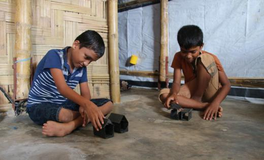 Banna*, 11, playing with his brother Arif*, 10, at their home in Cox's Bazar, Bangladesh