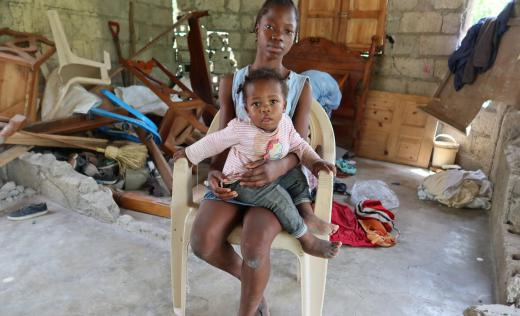 Nephtalie* (14) cradles her sister Gaelle* (18 months) on her lap in the remains of her destroyed house