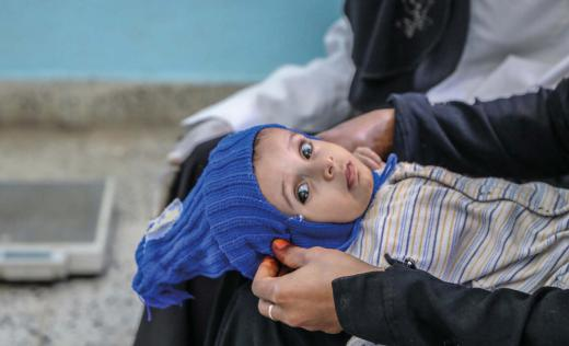 Suha*, 8 months old, held by her mother, in a health facility supported by Save the Children in Taiz governorate, Yemen