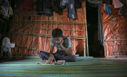 Tomal reads newspapers at his shelter