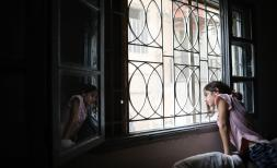 Lama*, 11, looks out the window of their house which was damaged during the Beirut explosion, Lebanon
