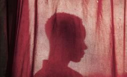 Former child soldier Nzitonda*, 14, sits behind a curtain in North Kivu, DRC.