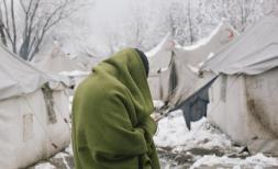 Refugee warming himself in blanket from sub zero temperatures at Vucjak camp / first snow of the year